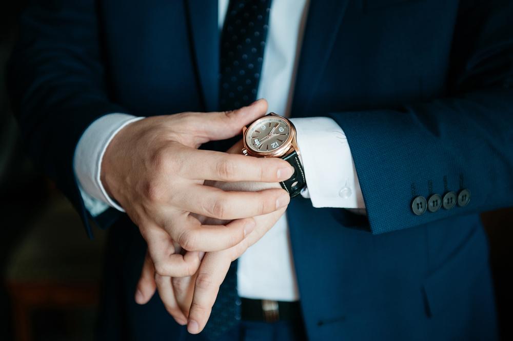 腕時計を触っているスーツの男性