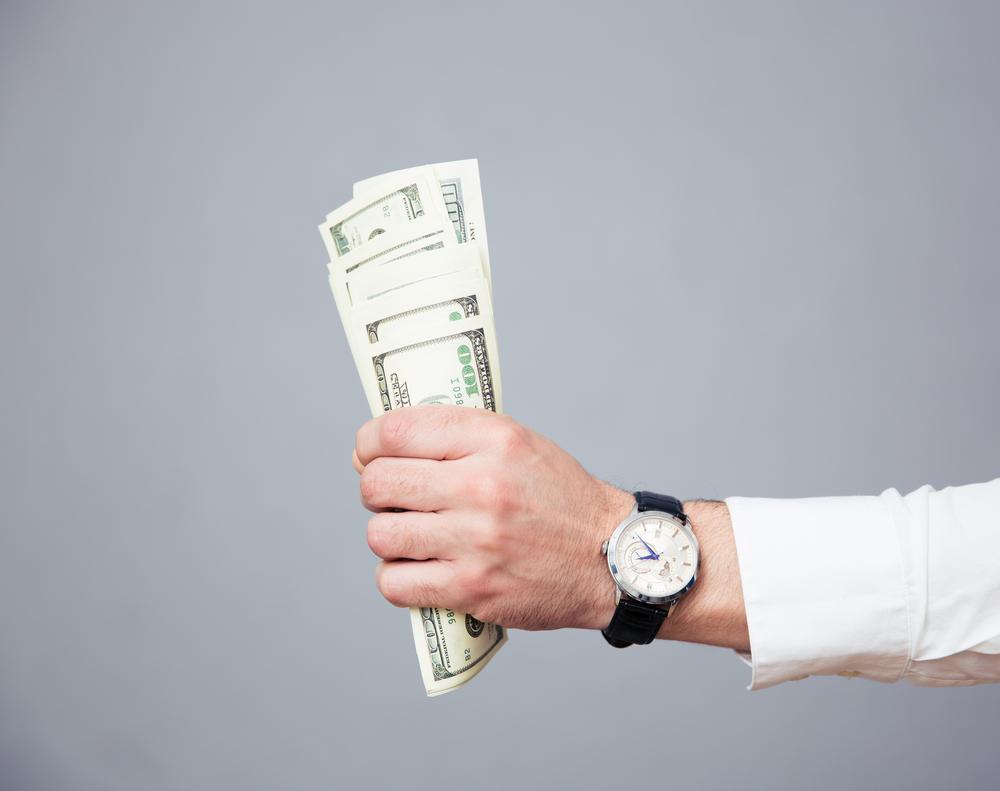 外国のお金を持った手と腕時計