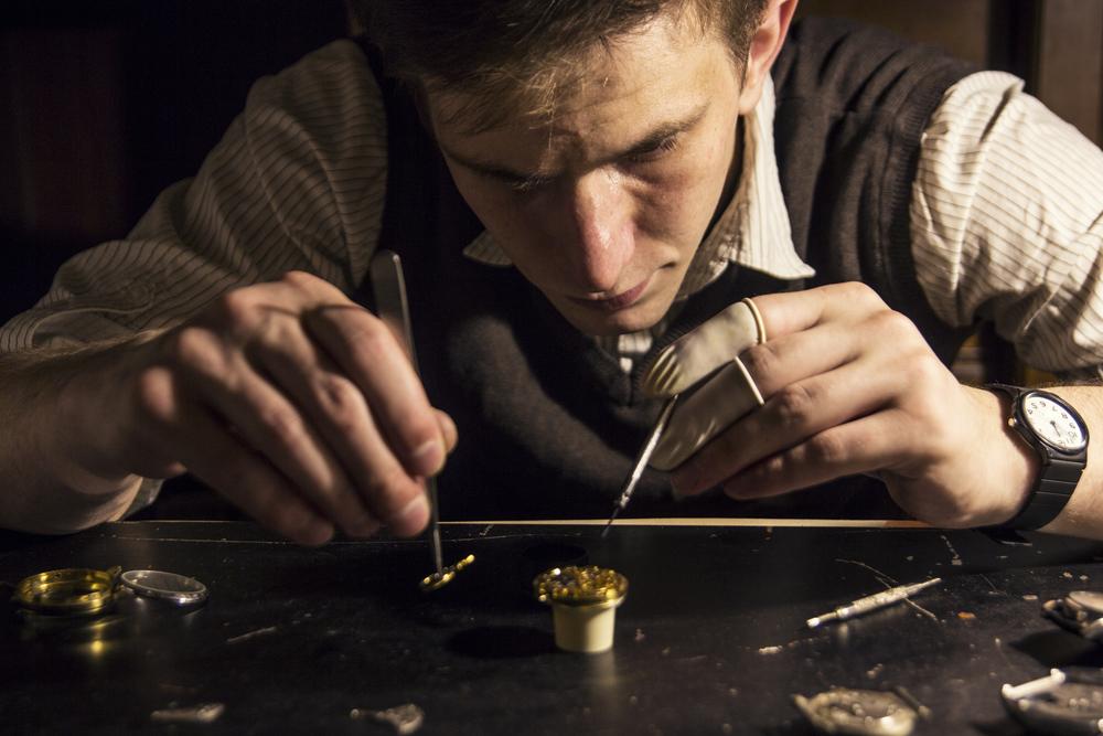 腕時計を修理している外国人