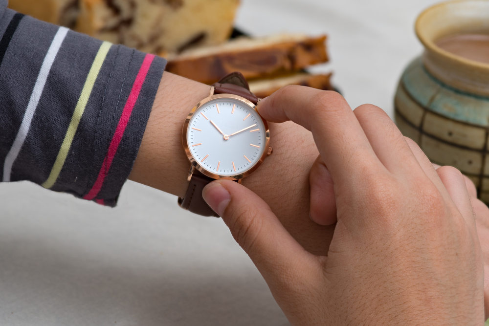 腕時計に手を添えている人