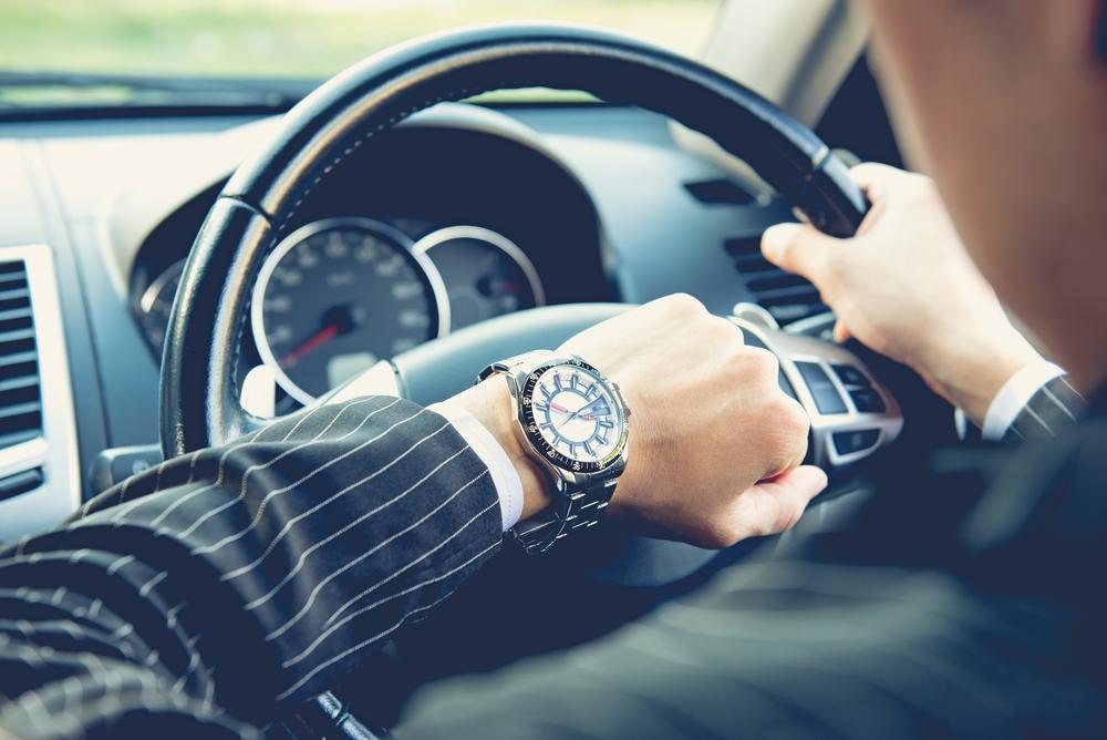 車内で腕時計を見ている男性